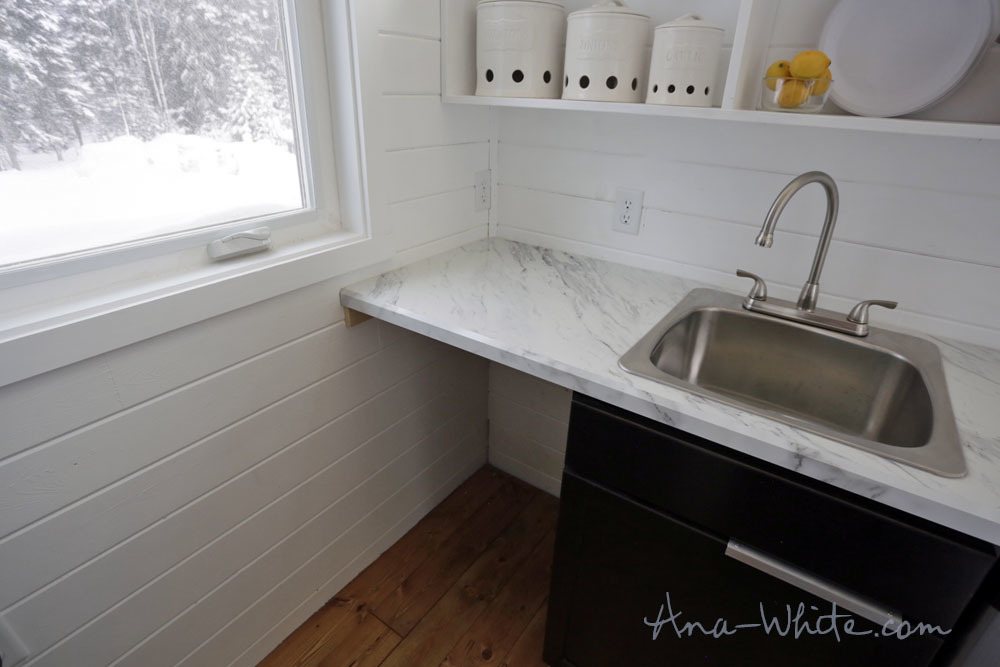 most notable being able to slide the kitchen cabinet under the window into the bathroom to reveal a hiding place in the kitchen corner for a washer dryer - Tiny House Washer Dryer