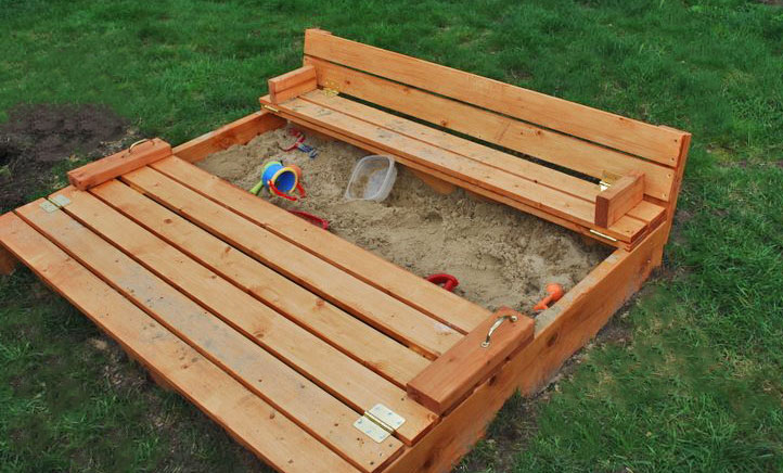 photo of stained wood sandbox with fold over cover that converts to seats