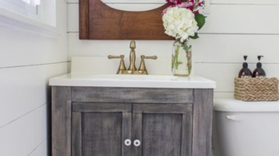 gray stained small bath vanity with turned legs and an open shelf with basket in white bathroom