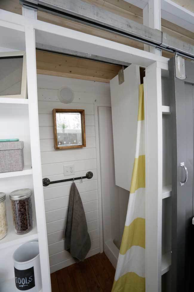 the closet is mounted on a sliding track and slides across the bathroom stored in the shower when not in use